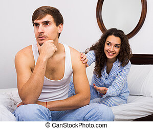 Smiling girl trying to comfort upset husband