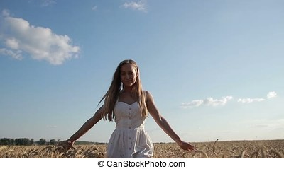 Smiling girl walking in spikes of wheat field