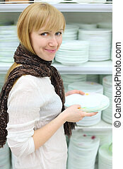 Smiling girl wearing scarf holds some white plates in shop; shallow depth of field
