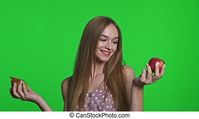 choosing between red apple and a pear fruit - Smiling girl ...