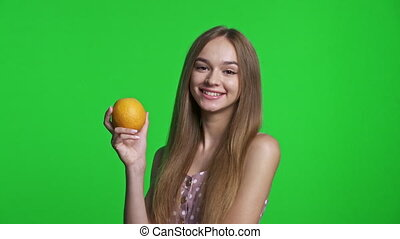 Smiling girl wearing summer dress holding an orange fruit, isolated over green chroma key background