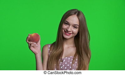 Smiling girl wearing summer dress smiling and holding a ripe peach, isolated over green chroma key background