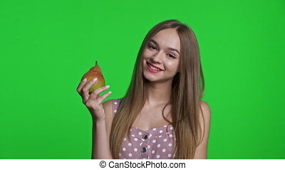 Smiling girl wearing summer dress smiling and holding a pear, isolated over green chroma key background