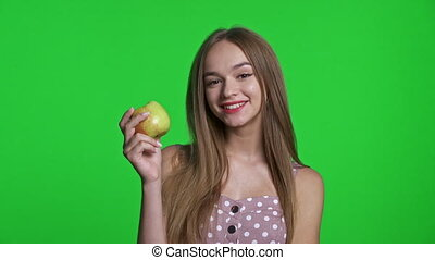 Smiling girl wearing summer dress smiling and holding green apple, isolated over green chroma key background
