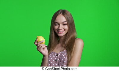 Smiling girl wearing summer dress smiling and holding lemon, isolated over green chroma key background