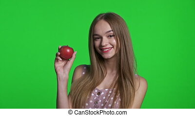 Smiling girl wearing summer dress smiling and holding red apple, isolated over green chroma key background