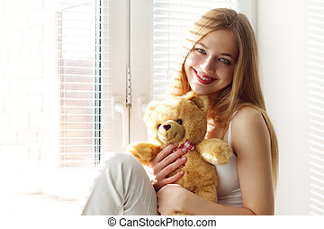 Smiling girl with a teddy bear at the window