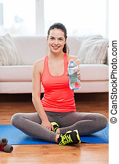 smiling girl with bottle of water after exercising -...
