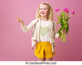 smiling girl with bouquet of tulips pointing at something