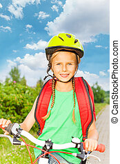 Smiling girl with braids in bicycle helmet