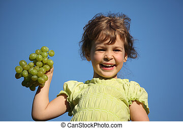 smiling girl with grape against blue sky