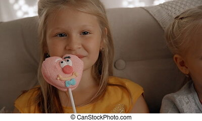 Smiling girl with happy face eating sweet candy snack -...