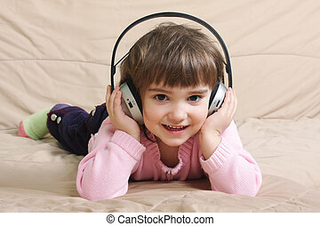 Smiling girl with headphones on sofa