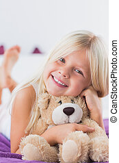Smiling girl with her teddy bear lying on a bed