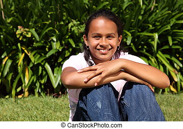 Smiling girl with knees up on grass