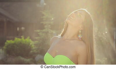 Smiling girl with long hair in jewelry in a bikini posing in the garden under spray of water at sunset