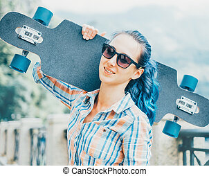 Smiling girl with longboard outdoor. - Smiling young woman...