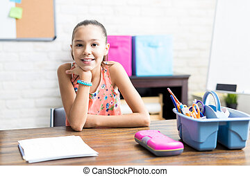 Smiling Girl With Notes Sitting At Table In House