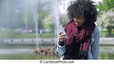 Smiling girl with phone on fountain