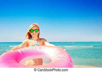 Smiling girl with pink swim ring on the beach