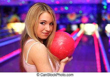 smiling girl with red ball stands in bowling club and ...