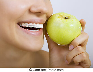 Beautiful smiling girl with retainer for teeth - healthy teeth and apple