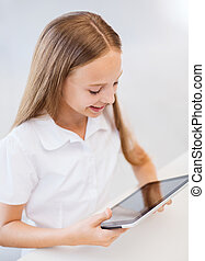smiling girl with tablet pc at school