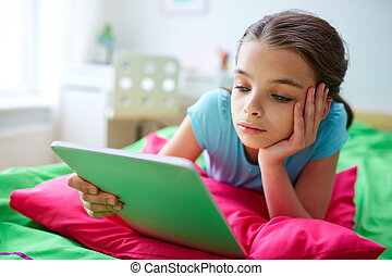 smiling girl with tablet pc lying in bed at home - children,...