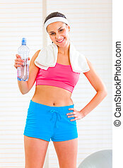 Smiling girl with towel around neck holding bottle of water