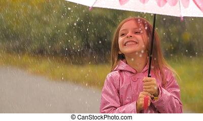 Smiling Girl With Umbrella Under Rain - Little girl is...