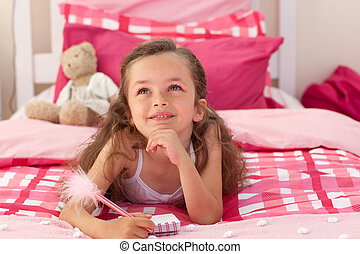 Smiling girl writing on bed