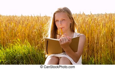 smiling girl writing to diary on cereal field - country,...