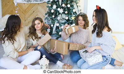 Smiling girlfriends present gifts each other. Christmas mood