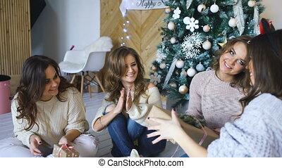 Smiling girlfriends talking near christmas tree. Xmas mood.