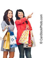 Smiling girls at shopping pointing up