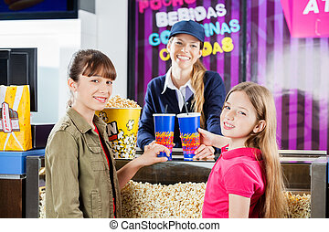 Smiling Girls Buying Popcorn And Drinks From Seller At Cinema