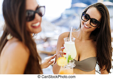 Smiling girls drinking cocktails