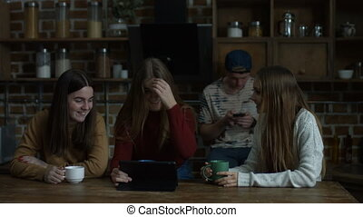 Smiling girls gossiping about male friend in kitchen -...