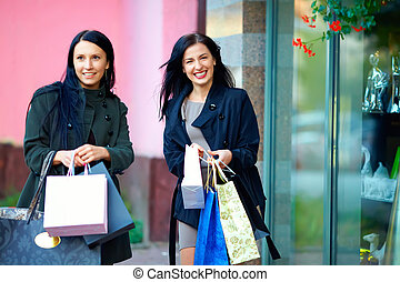 smiling girls shopping in the city