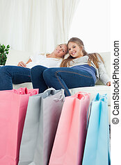 Smiling girls sitting on the couch with their bags of shopping
