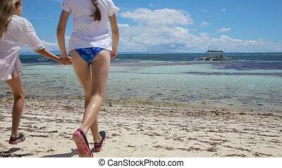 smiling girls splashing and running in the sea.
