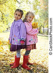 Smiling girls standing back-to-back in autumn park