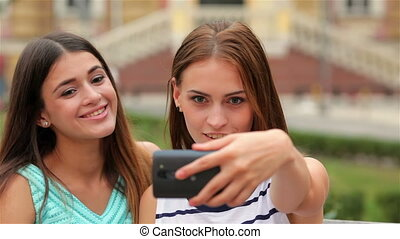 Smiling girls taking selfie with smartphone camera