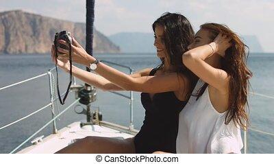 Smiling girls with camera taking selfie