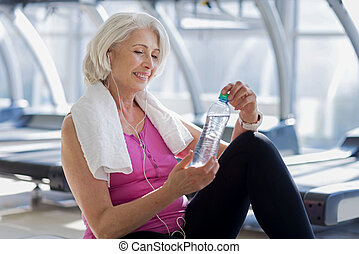Smiling glad woman sitting on a floor and holding water.