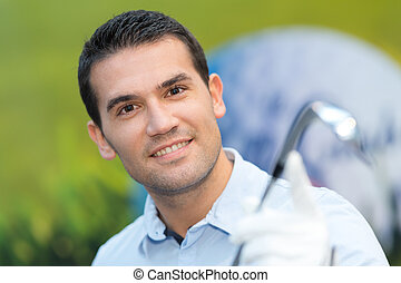 smiling golf player standing on field