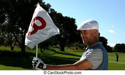 Smiling golfer holding eighteenth hole flag on golf course...
