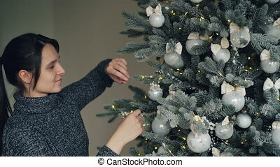 Smiling good-looking girl is decorating New Year tree before...