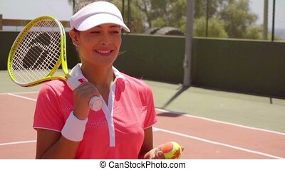 Smiling gorgeous trendy young tennis player
