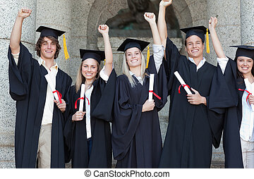 Smiling graduates posing while raising arms